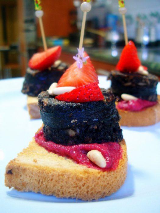 Pincho de Morcilla con crema de remolacha, fresas y piñones