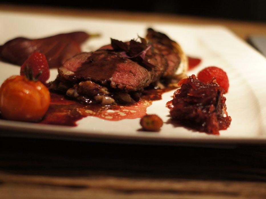 Magret de pato sobre salsa de boletus con pera al vino, cebolla roja caramelizada, endivia y frutos rojos