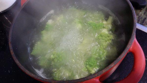 Cuando veamos que empieza a hervir el agua echamos las hojas y los ramilletes más grandes. Dejamos cocer de tres a cinco minutos. Contados una vez el agua comience de nuevo a hervir.
