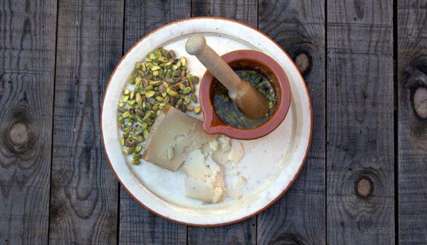 Mientras preparamos la picada de pistachos y queso de oveja curado. Para ello machacamos un poco los pistachos en un mortero. Añadimos el aceite y el queso. Machacamos nuevamente unos segundos.