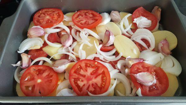 Cortamos en rodajas no muy gruesas el tomate y la cebolleta. Colocamos encima de la patata.